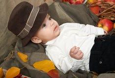 秋天在黄色秋天叶子、苹果、南瓜和装饰的小男孩谎言在纺织品 免版税图库摄影
