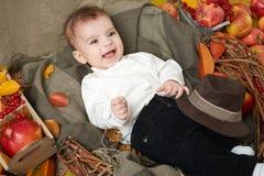 秋天在黄色秋天叶子、苹果、南瓜和装饰的小男孩谎言在纺织品 免版税库存照片