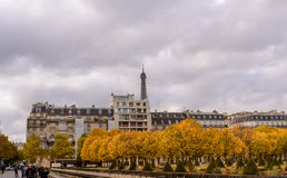 秋天在巴黎,镇在背景埃佛尔铁塔的黄色树中回家 图库摄影