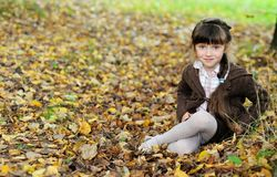 秋天地毯儿童逗人喜爱女孩叶子坐 免版税图库摄影