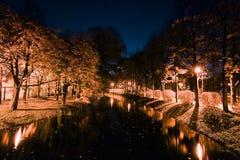 秋天城市公园在晚上 树、河和街灯 库存图片
