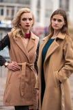 秋天外套的两个美丽的女孩 免版税库存图片