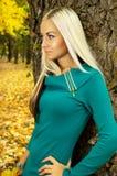 秋天天气倾斜的美丽的金发碧眼的女人在树 图库摄影