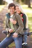 秋天夫妇循环公园纵向年轻人 免版税库存照片