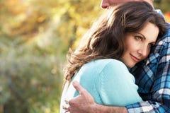 秋天夫妇拥抱浪漫森林地 免版税库存照片