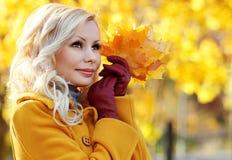 秋天女孩。有槭树叶子的时尚白肤金发的美丽的妇女 库存图片