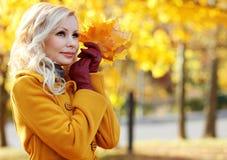 秋天女孩。有槭树的时尚白肤金发的美丽的妇女离开  免版税图库摄影