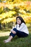 秋天女孩草坪坐的一点 免版税库存图片