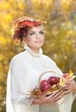 秋天妇女。美好的创造性的构成和发型在室外射击。有叶子的女孩在拿着一个篮子用苹果的头发 免版税库存图片