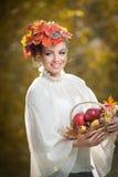 秋天妇女。美好的创造性的构成和发型在室外射击。有叶子的女孩在拿着一个篮子用苹果的头发 免版税图库摄影