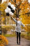 秋天妇女在有气球的秋天公园 灰色外套的时尚女孩 免版税库存照片