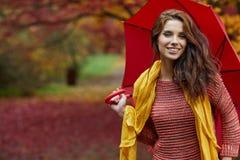 秋天妇女在有红色伞、围巾和皮革的秋天公园 库存图片