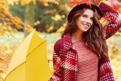 秋天妇女在有红色伞、围巾和皮革的秋天公园 免版税库存照片