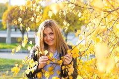 秋天妇女纵向有黄色叶子的 库存图片