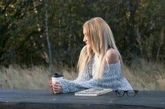秋天妇女饮用的咖啡 享受从一次性咖啡杯的少妇的秋天概念热的饮料 库存图片
