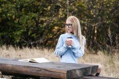 秋天妇女饮用的咖啡 享受从一次性咖啡杯的少妇的秋天概念热的饮料 免版税库存照片