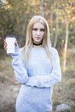 秋天妇女饮用的咖啡 享受从一次性咖啡杯的少妇的秋天概念热的饮料 免版税图库摄影