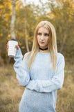 秋天妇女饮用的咖啡 享受从一次性咖啡杯的少妇的秋天概念热的饮料 库存照片