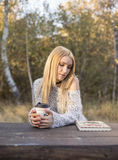 秋天妇女饮用的咖啡 享受从一次性咖啡杯的少妇的秋天概念热的饮料 免版税库存图片