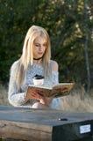 秋天妇女饮用的咖啡 少妇的秋天概念 免版税库存照片