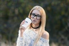 秋天妇女饮用的咖啡 少妇的秋天概念 图库摄影