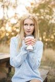秋天妇女饮用的咖啡 秋天概念 免版税库存图片