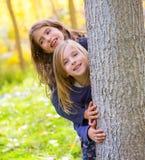 秋天姐妹使用在森林树干的孩子女孩室外 免版税图库摄影