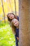 秋天姐妹使用在森林树干的孩子女孩室外 图库摄影