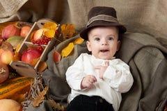 秋天季节、儿童男孩谎言在黄色秋天叶子,苹果、南瓜和装饰在纺织品 免版税库存照片