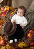 秋天季节、儿童男孩谎言在黄色秋天叶子,苹果、南瓜和装饰在纺织品 库存照片