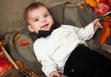 秋天季节、儿童男孩谎言在黄色秋天叶子,苹果、南瓜和装饰在纺织品 库存图片