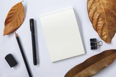 秋天季节工作区顶视图 黑笔和铅笔 笔记薄空白页白皮书  库存照片