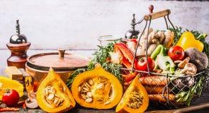 秋天季节性烹调概念 各种各样的秋天季节性有机菜:南瓜,红萝卜,辣椒粉,在篮子的姜与烹调 免版税图库摄影