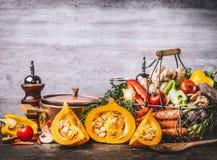 秋天季节性食物静物画用南瓜,蘑菇,各种各样的有机收获菜和烹调罐在土气厨房tabl 免版税图库摄影
