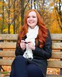 秋天季节的女孩在城市公园、黄色树和下落的叶子听在音频球员的音乐有耳机的,坐长凳 免版税图库摄影