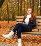 秋天季节的女孩在城市公园、黄色树和下落的叶子听在音频球员的音乐有耳机的,坐长凳 库存照片