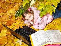 秋天孩子膝上型计算机离开桔子 库存图片