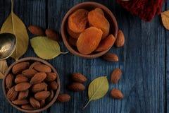 秋天安排用杏仁杏干和一条温暖的围巾和黄色叶子在一张深蓝木桌上 库存图片