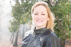 秋天室外微笑的白肤金发的妇女 库存图片