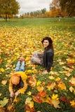 秋天家庭在户外秋天公园 愉快的母亲和儿童男孩 免版税库存照片