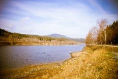 秋天山有湖视图和叶子在森林里 库存照片
