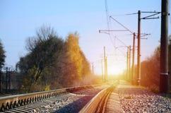 秋天工业风景 后退入在绿色和黄色秋天树中的距离的铁路 库存图片