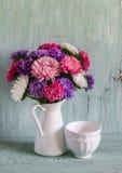 秋天开花在一个白色搪瓷水罐和白色陶瓷碗的翠菊轻的木表面上 库存图片