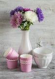 秋天开花在一个白色花瓶、陶瓷碗和纸模子的翠菊烘烤的蛋糕的,在葡萄酒样式的静物画 库存图片