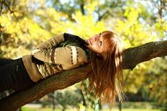 秋天微笑的女孩纵向位于在结构树的 图库摄影