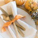 秋天感恩或万圣夜表餐位餐具和南瓜在金子口气 与温暖的自然照明设备的正方形从lookin上 库存图片