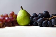 秋天成熟蓝色和红葡萄收获板材在背景的用梨 免版税库存照片