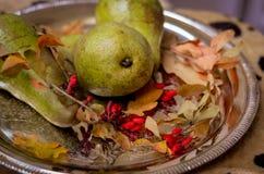 秋天成熟绿色梨,黄色在一个银色盘子离开 免版税库存图片