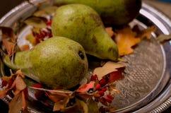 秋天成熟绿色梨,黄色在一个银色盘子离开 图库摄影