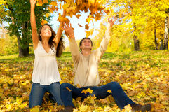 秋天投掷年轻人的夫妇叶子 库存照片